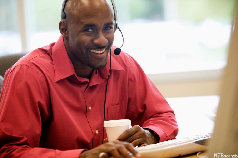 Bilde av en mann på et kontor som sitter og snakker med hodetelefoner foran en datamaskin