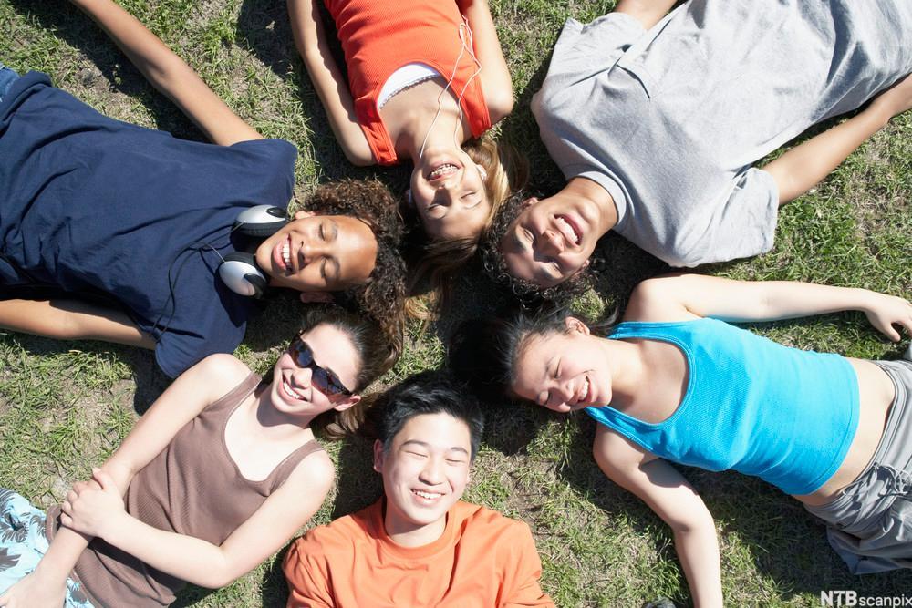 Bildet viser en gruppe ungdommer som ligger på en plen. Foto.