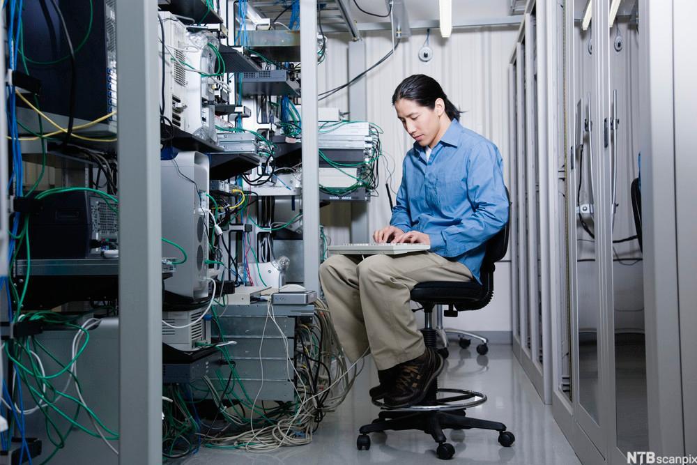 Mann sitter og jobber ved serverrack. Foto