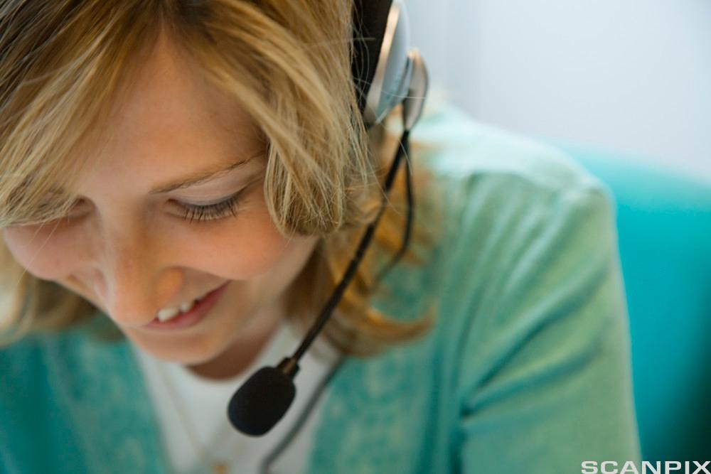 Kvinne med hodetelefon. Foto.