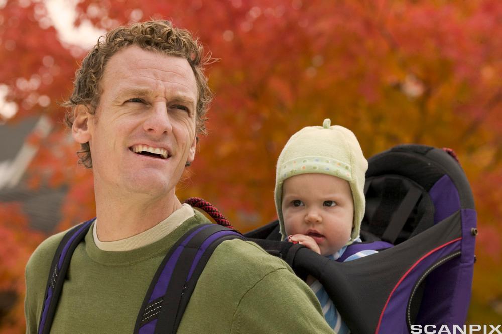 En far bærer sitt barn på ryggen. Foto.