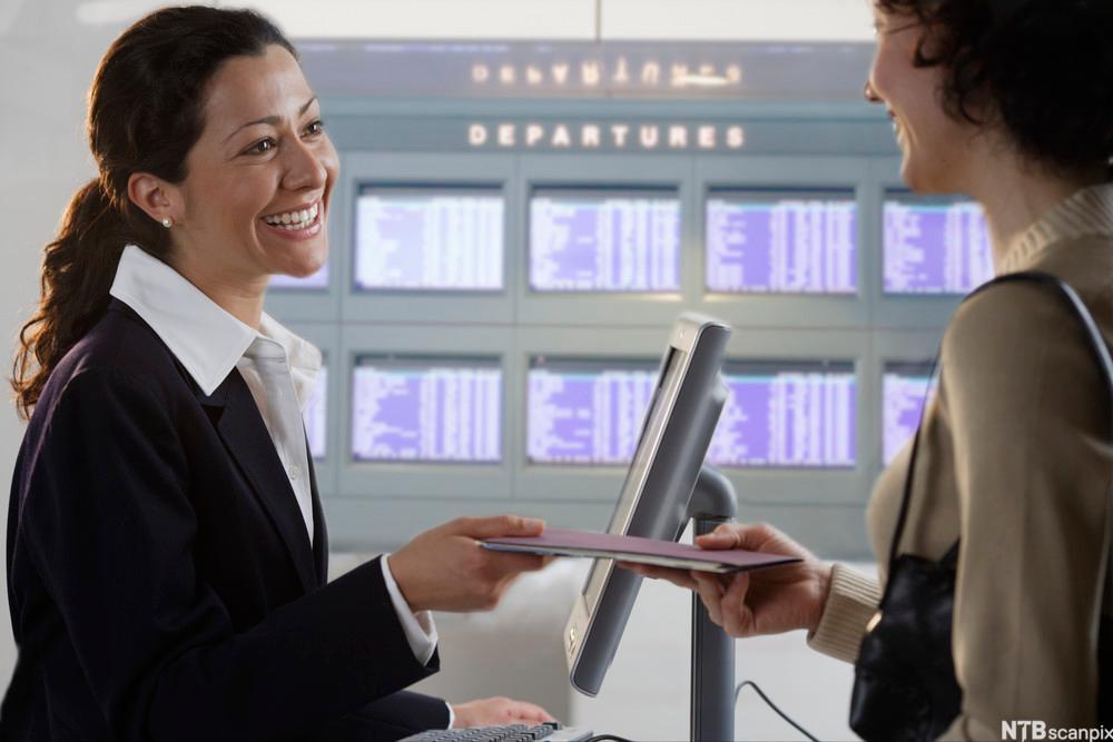 En reisende får overlevert billetter av en medarbeider ved en skranke på en flyplass. På veggen bak dem henger dataskjermer med lister over avgangstider. Foto.