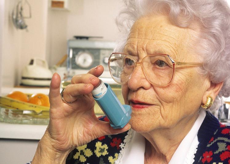 Eldre kvinne med astma inhalator. Foto.
