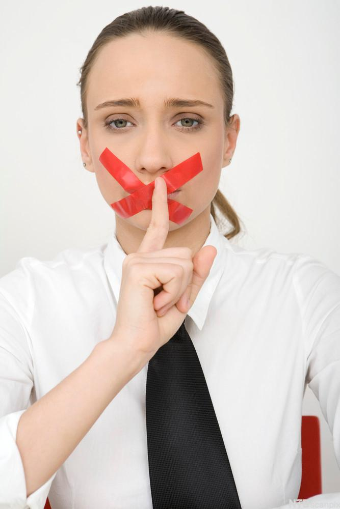 Kvinne med rød tape over munnen som hysjer med fingeren. Foto.