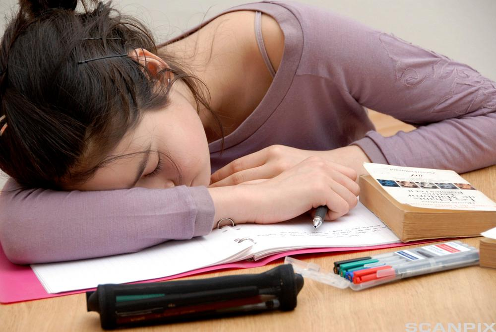 Jente sitter lent over bøker på et bord og sover.foto.