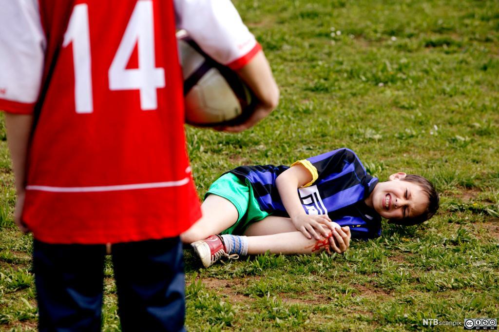 Gutt ligger med skadet kne på fotballbanen. Foto.
