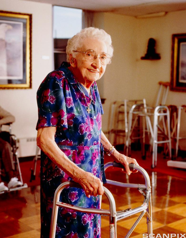 Eldre kvinne bruker gåstol på aldershjem. Foto.