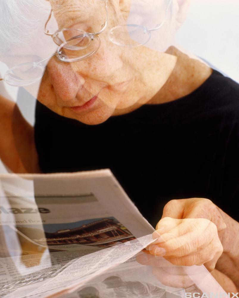 Mann med Parkinson leser avis. foto.