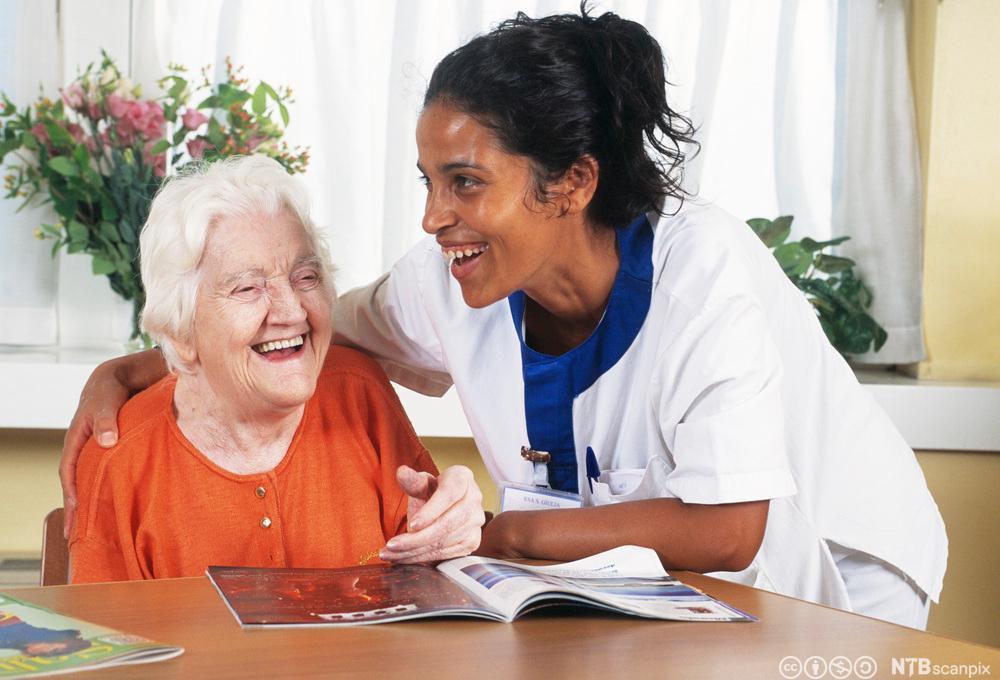 Beboer og helsefagarbeider som ler sammen. Foto.