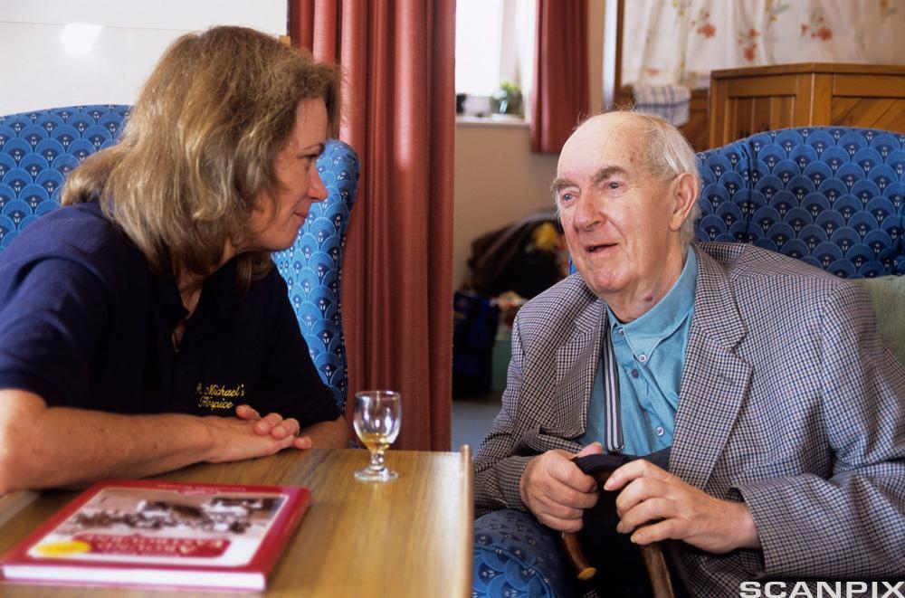 Bildet viser ein mann som pratar med ein pleiar på eit eldresenter