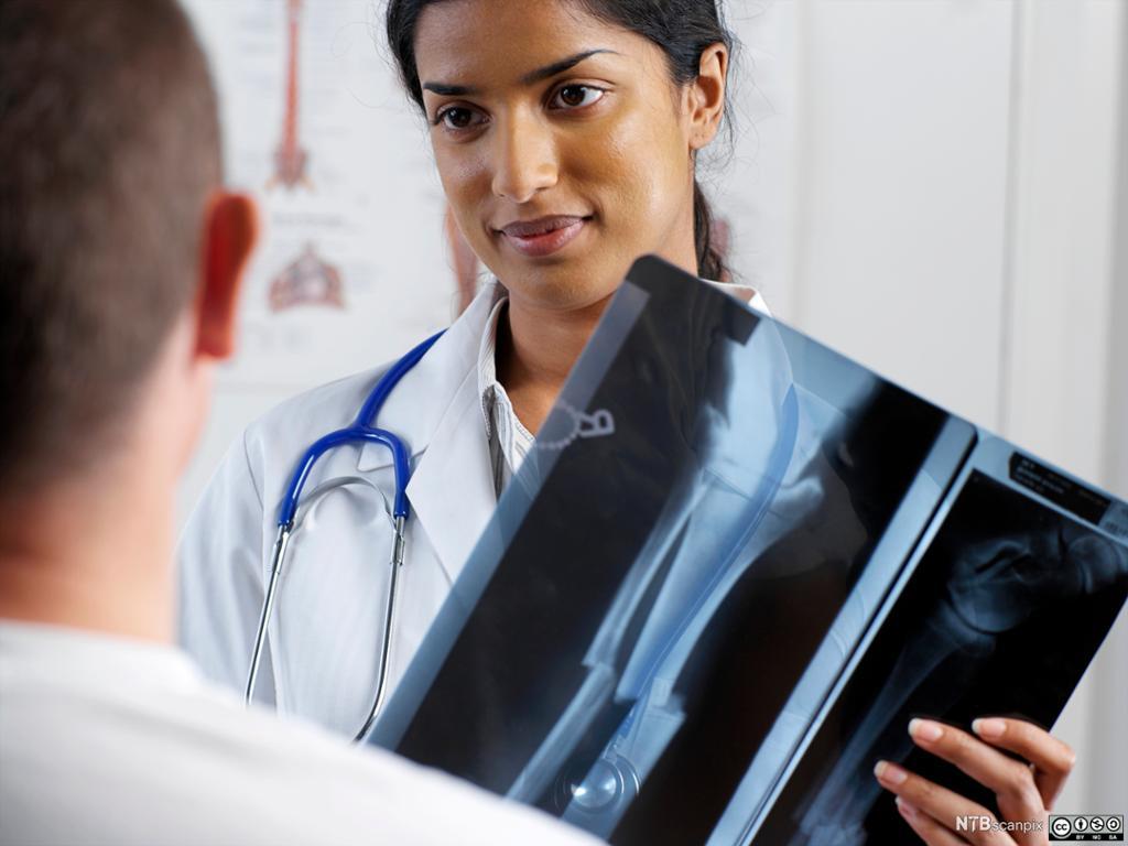 En kvinnelig lege viser et røntgenbilde til en mann som har brekt foten. Foto.