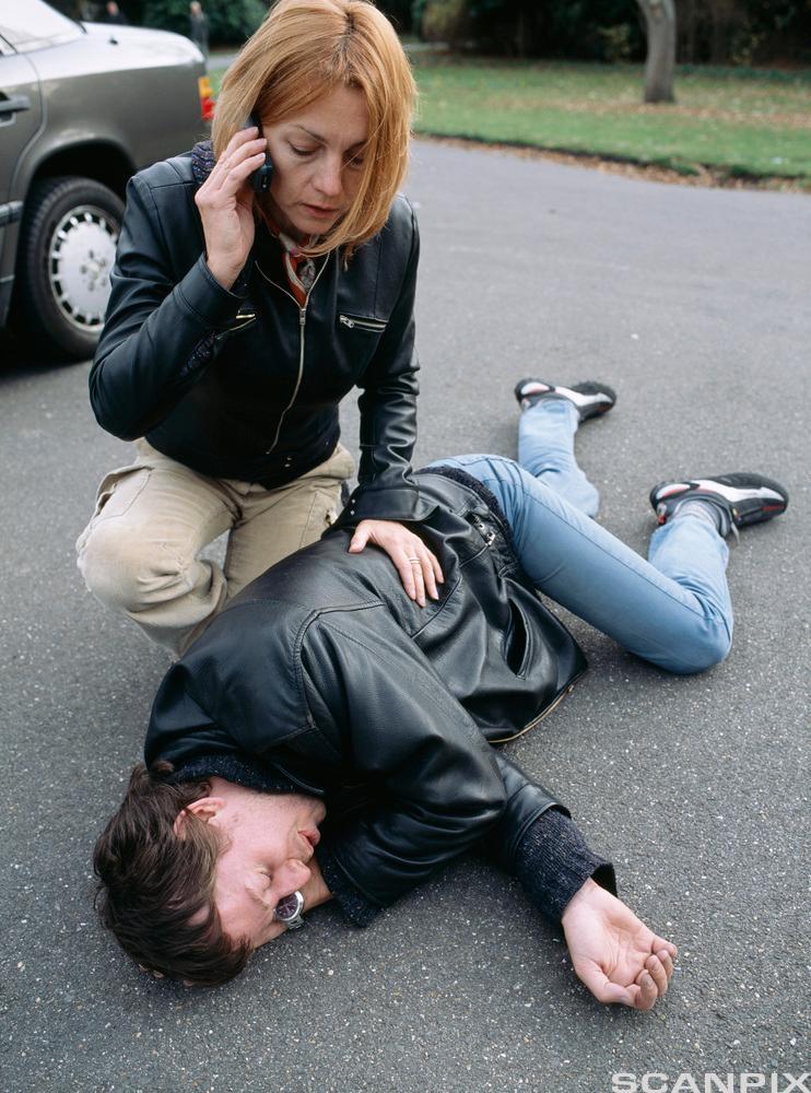 Kvinne tar seg av skadet mann. Foto.
