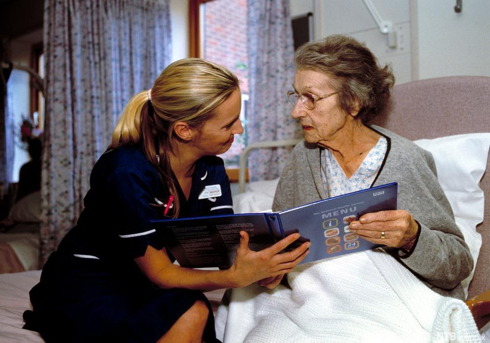 Bilde av en eldre kvinne som får hjelp av en sykepleier til å lese i en sykehus meny