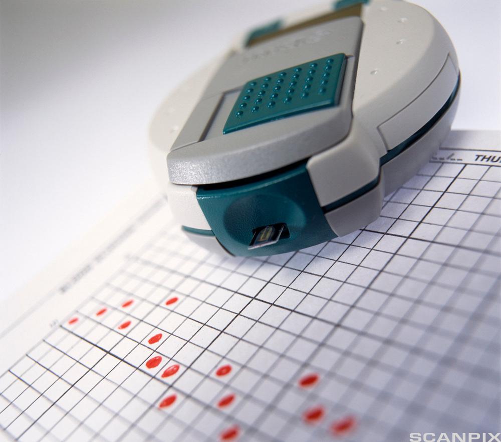 Bildet viser et apparat som måler blodsukker og et notat