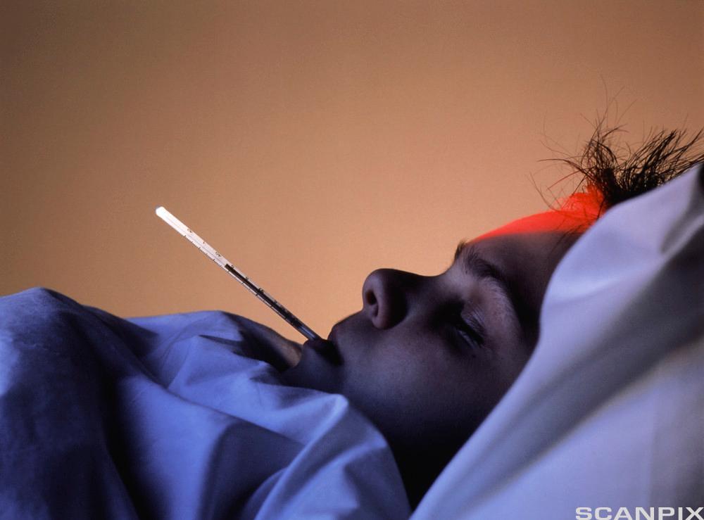Gutt ligger i sengen med temparaturmål i munnen. Foto.