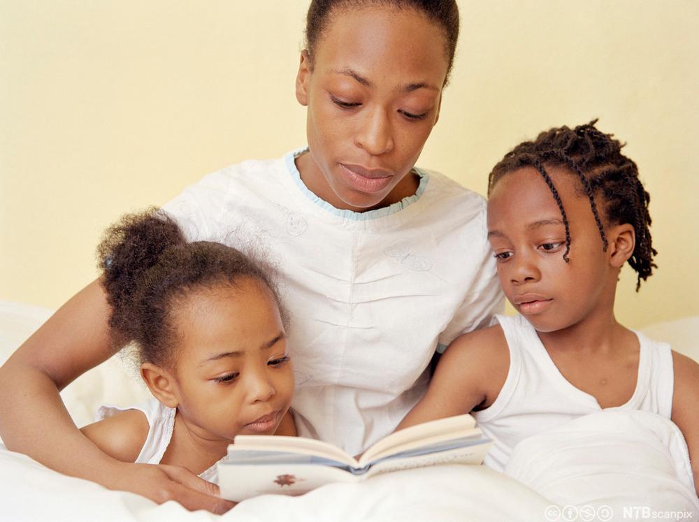 Mor leser høyt for barna sine. Foto.