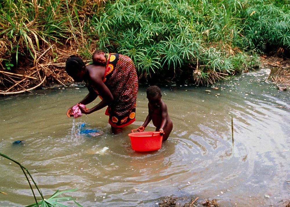 Kvinne med barn vasker klær i en dam. Foto.