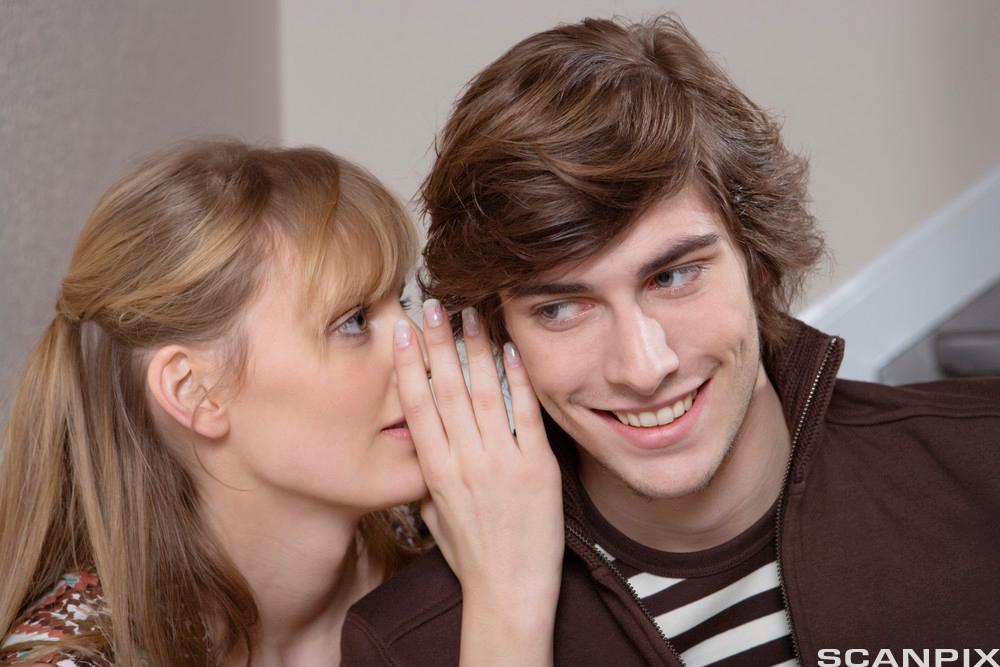 Kvinne som visker i øret til en mann.Foto.