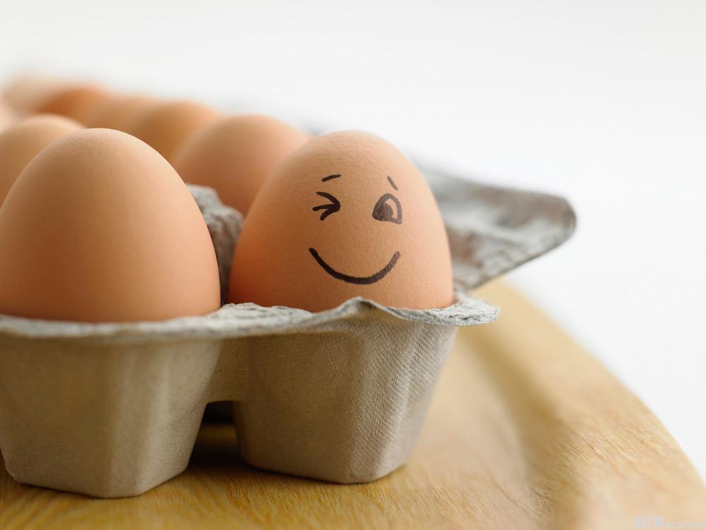 """En åpen eggekartong med et """"smilende"""" egg i. Foto."""