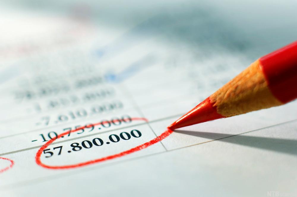 Sumlinje i et regnskapskjema blir ringet rundt med rød blyant. Foto.
