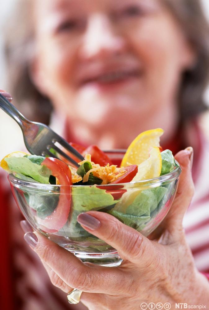 Eldre kvinne et ein salat. Foto.