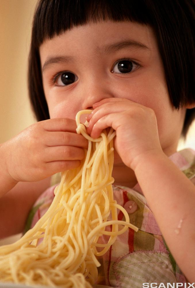 Jente spiser spaghetti. Foto.