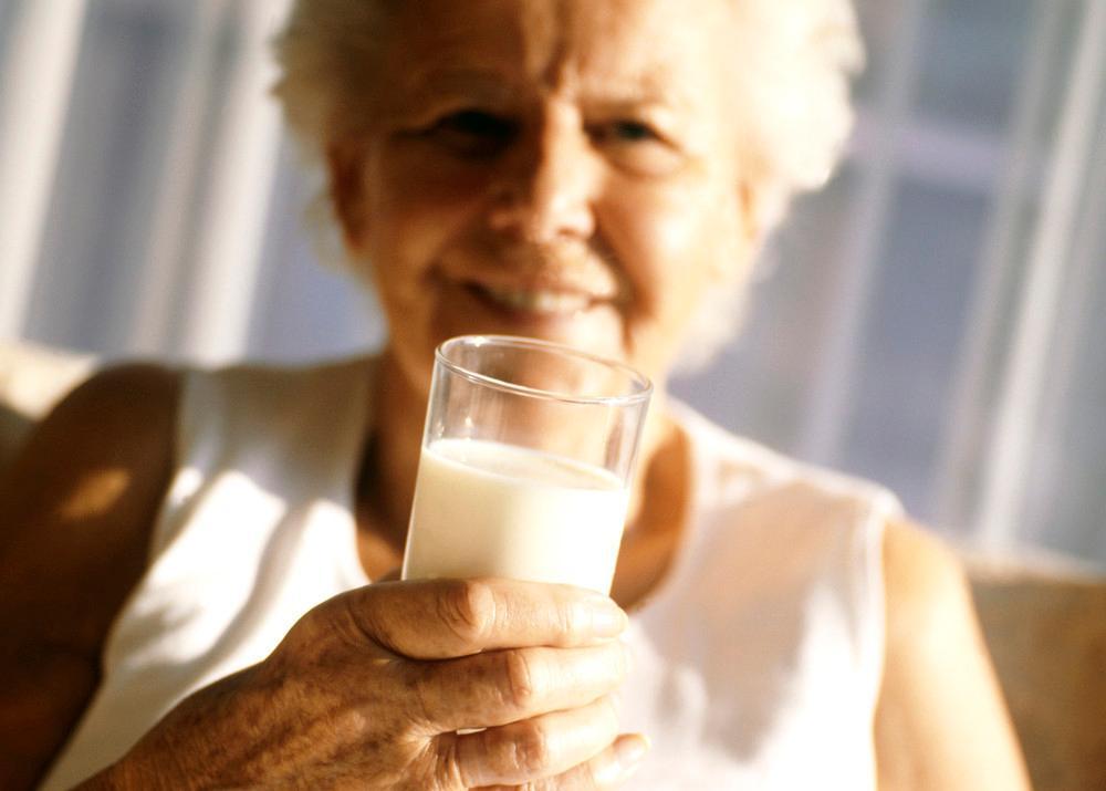 Eldre kvinne drikker melk. Foto.