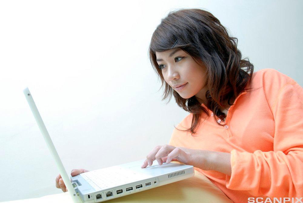Jente bruker bærbar datamaskin. Foto.