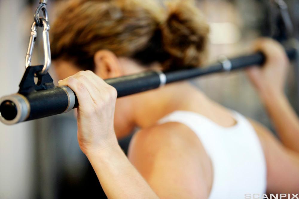 Jente trener styrke med et apparat. Foto.
