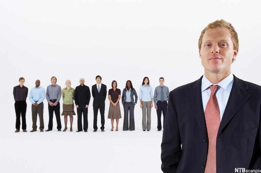 Bilde av en sjef og ansatte der sjefen står fremst i bilde i dress og de ansatte står på en linje noen meter bak ham
