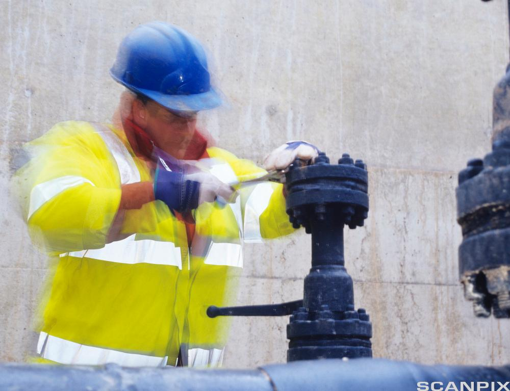 Arbeider i verneutstyr reparerer gassrør. foto.