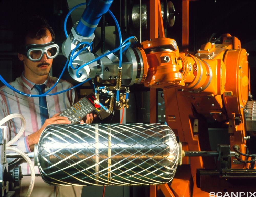 En tekniker som sveiser en robotarm i plastmateriale