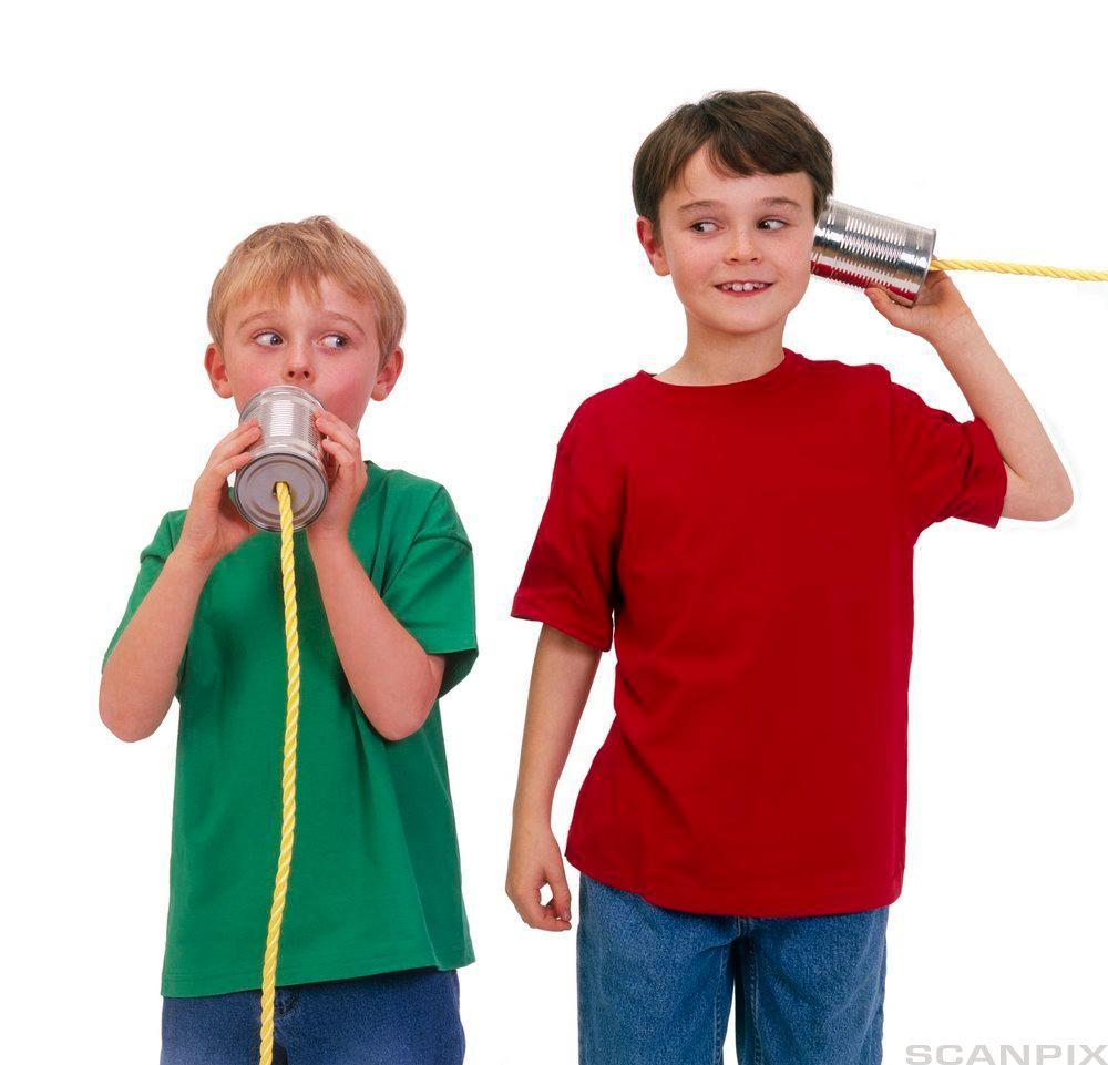 To gutar som snakkar i telefonar laga av hermetikkboksar. Foto.