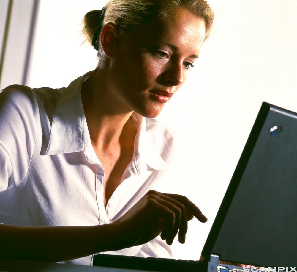 kvinne skriver på pc. Foto.