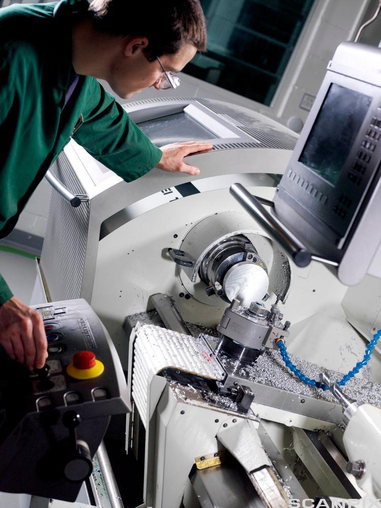 Metallarbeider justerer kontrollene på en CNC dreiebenk. Foto.