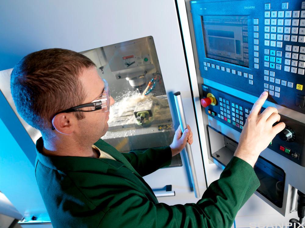 Metallarbeider opererer en CNC fresemaskin. Foto.
