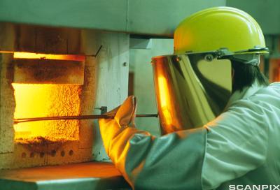 Arbeider i smelteovn med skikkerhetsutstyr. foto.