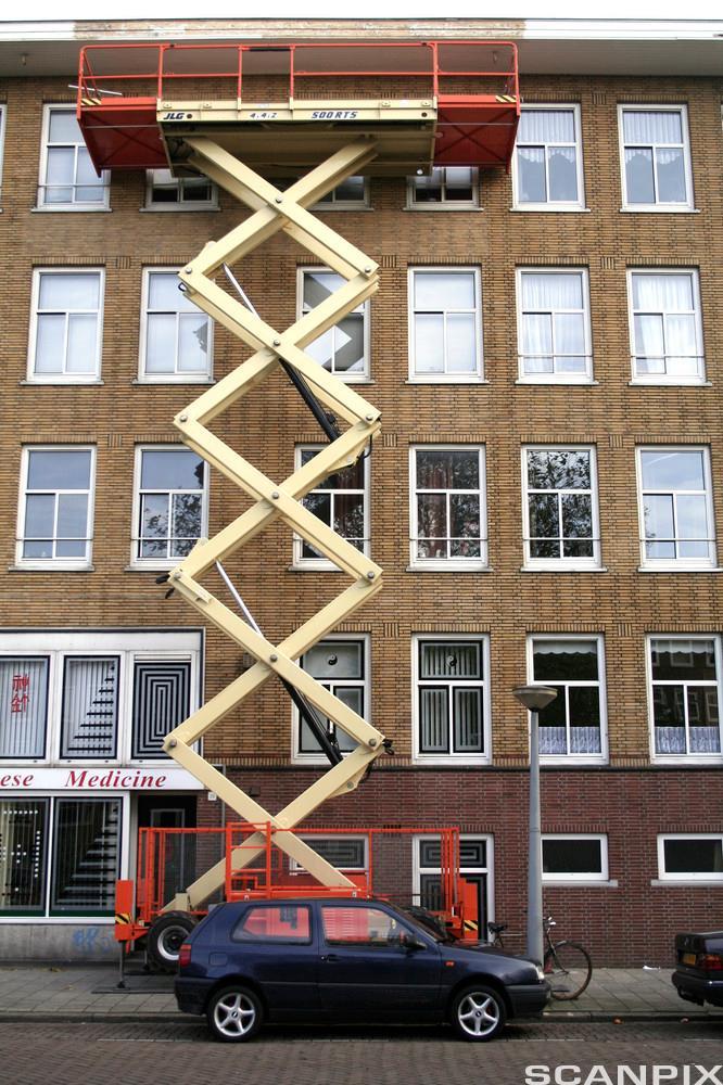 Lift på saksheis utenfor hus med mange etasjer. foto.
