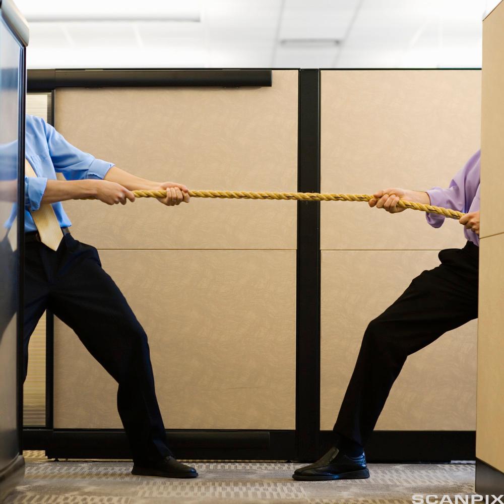 Tautrekking mellom to menn på et kontor. Foto.