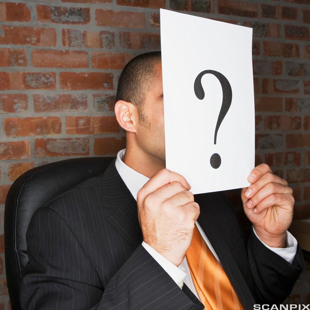 mann som holder et spørsmålstegn framfor annsiktet.foto.
