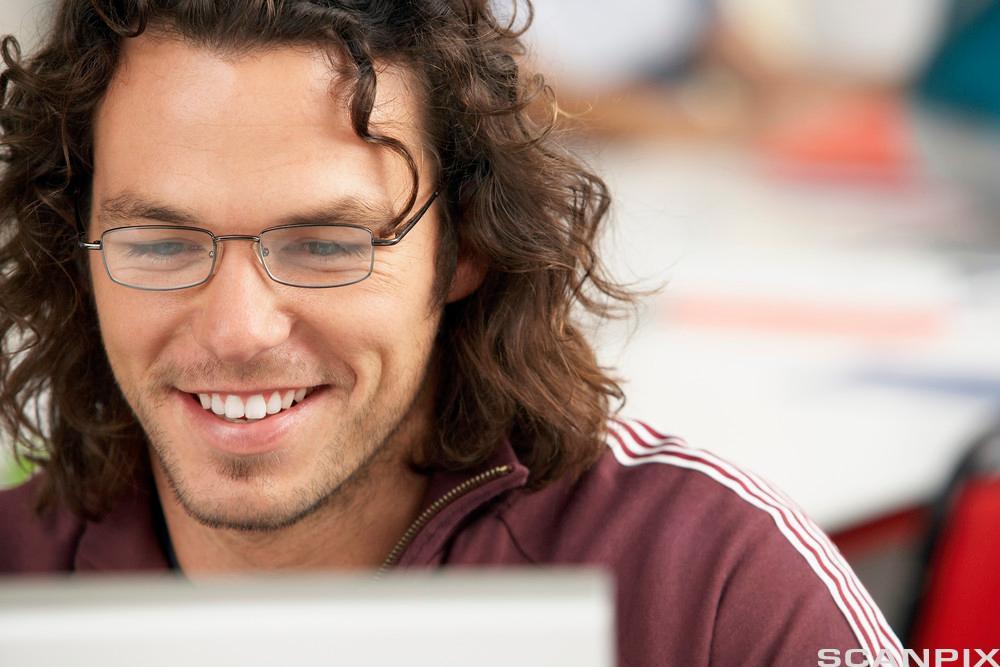 Ung mann bruker datamaskin. Foto.