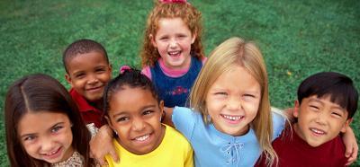 Seks barn står sammen og smiler mot kameraet. Foto.