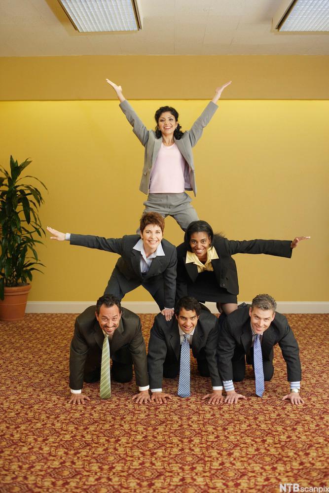 Bilde av seks mennesker som har formet en pyramide med tre nederst, to i midten og en person øverst som strekker hendene i luften.