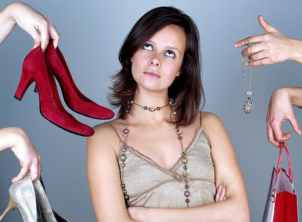 Bilde av en kvinne med armene i kors og ser uinteressert på sko, smykke og vesker som blir holdt opp foran henne