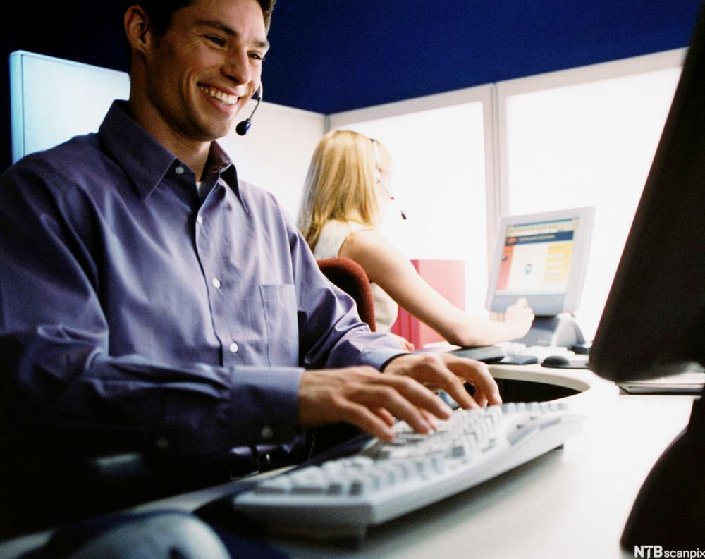 Kundeservicemedarbeider som sitter ved datamaskin. Foto.