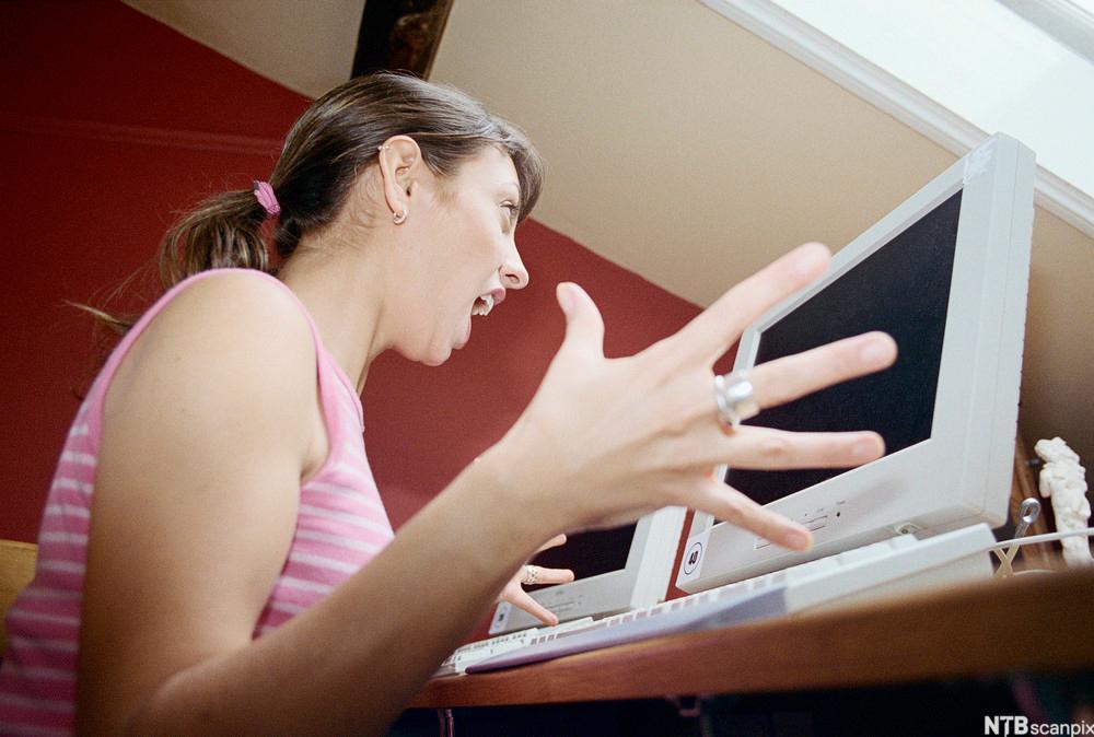Kvinne som er tydelig frustrert sittende foran en pc. Foto.