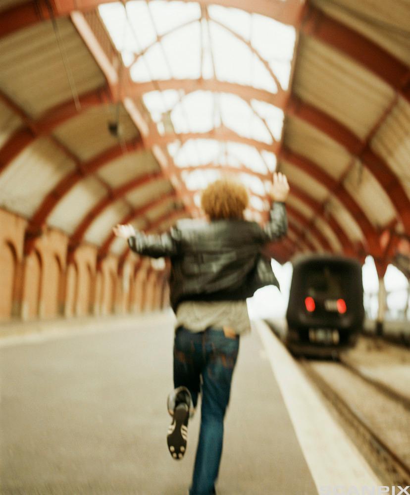 Bilde av en mann som løper etter et tog.