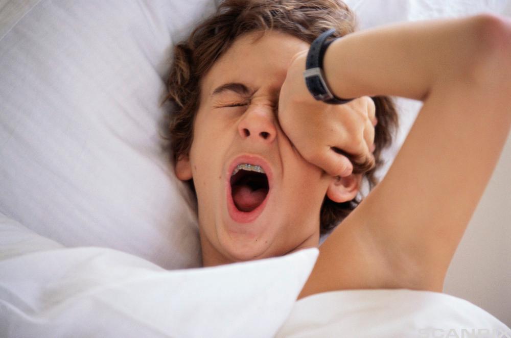 Gutt som ligger i senga og gjesper.Foto.