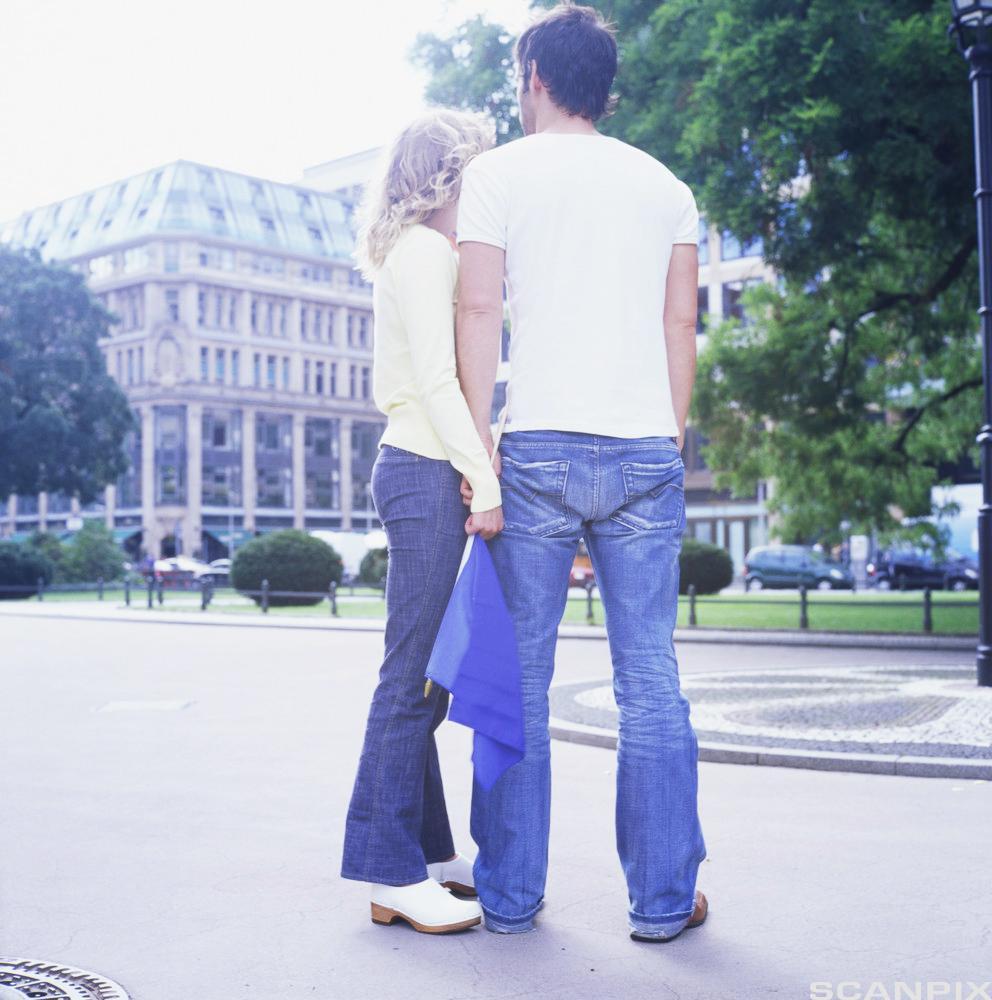 Ungt par stående på gaten. Foto.