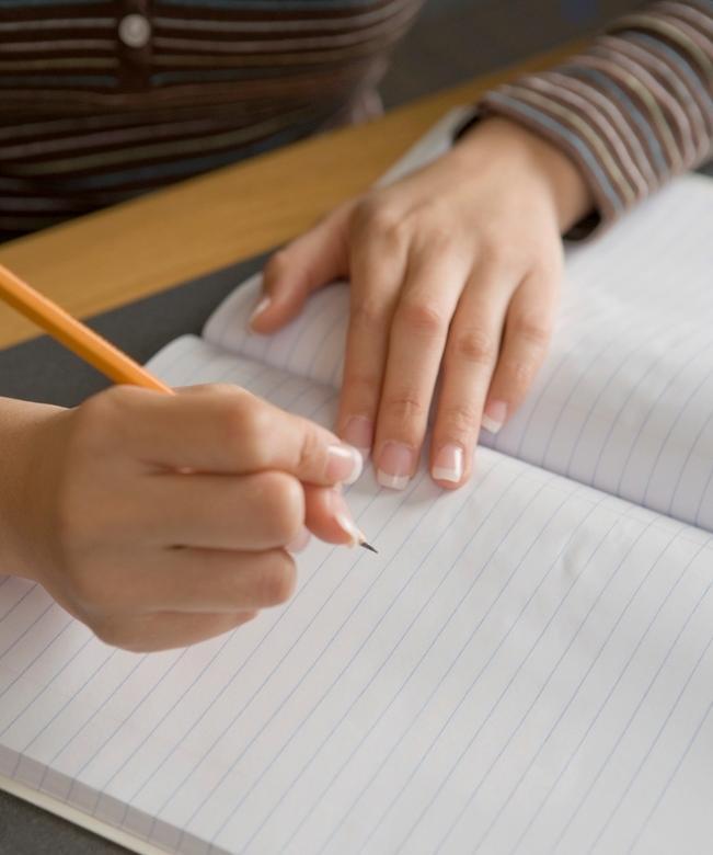 Person skriv på eit ark. Foto.